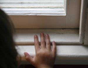 Picture of a child's hand on an old window frame